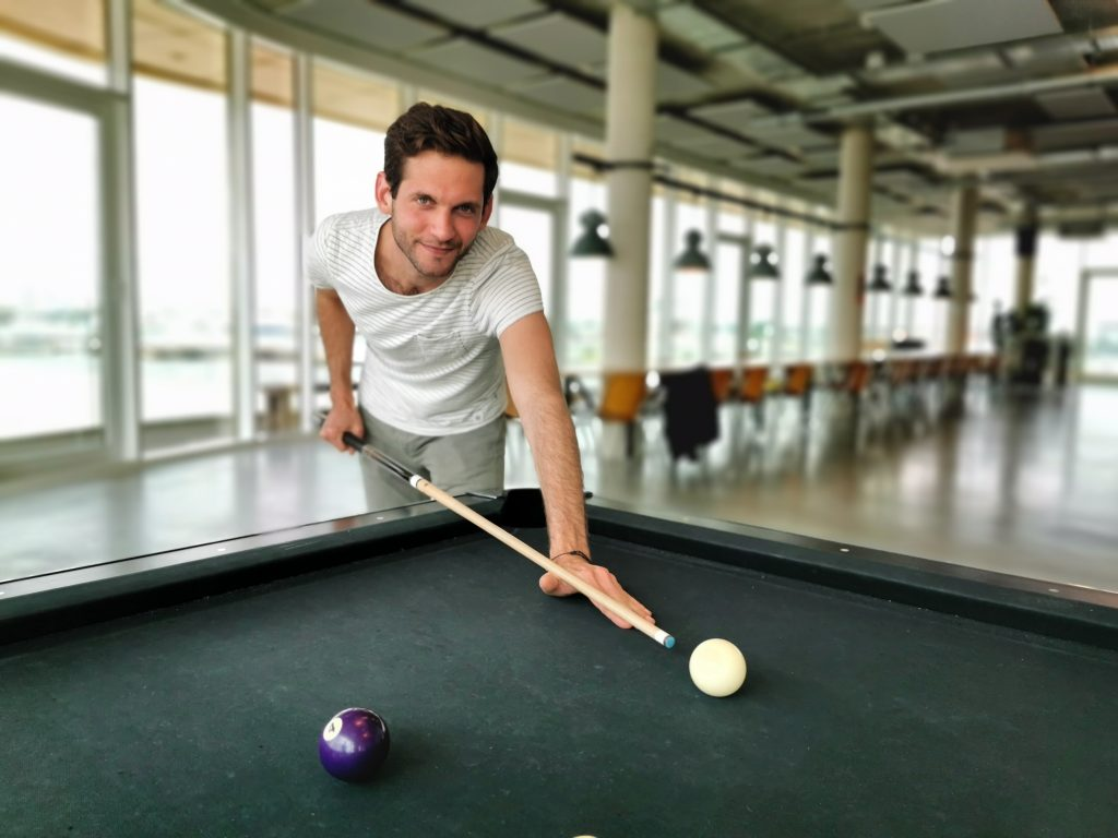 Business Analyst Lucas Lôbo playing pool at Emakina